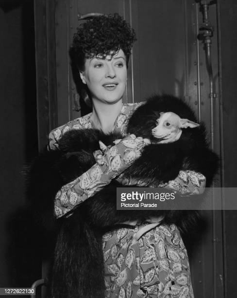 American burlesque entertainer and actress Gypsy Rose Lee with her pooch Topsy wrapped in a black fur shawl arrive in New York City, US, 1944.
