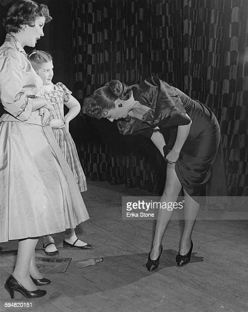 American burlesque entertainer Gypsy Rose Lee inspects a run in her stocking whilst appearing in the play 'The Women' circa 1953
