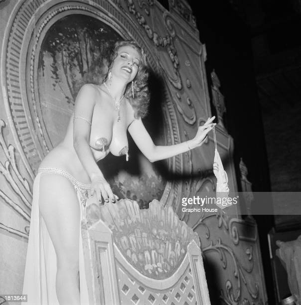 American burlesque stripper Tempest Storm removes her bra while performing on stage 1954