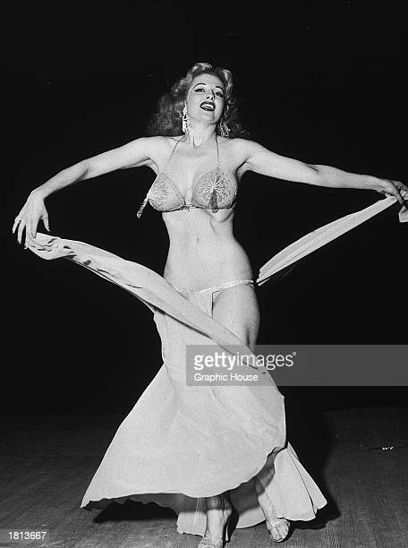 American burlesque stripper Tempest Storm twirls her skirts while performing c 1954