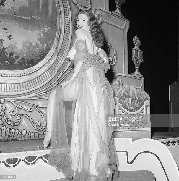 American burlesque stripper Tempest Storm wears a sheer dressing gown and sequins on her nipple while posing on stage 1954