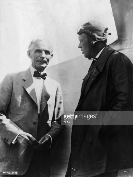 American businessman and automobile manufacturer Henry Ford talks with pilot Charles A. Lindbergh , dressed in a long coat and flight helmet, as they...