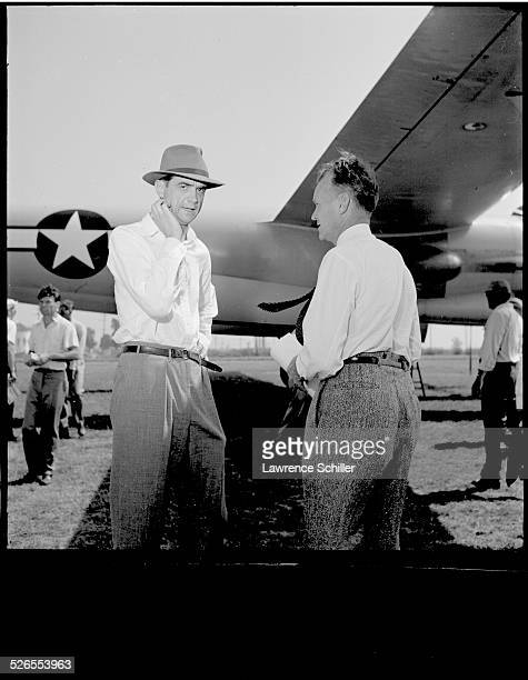 American businessman and aviator Howard Hughes speaks with an unidentified man by the fuselage of a US military plane Long Beach California 1947