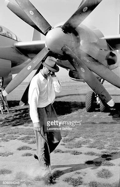 American businessman and aviator Howard Hughes walks past the propeller of one of his airplanes Los Angeles California 1947