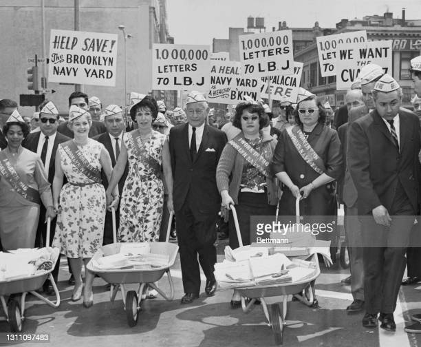 American businessman and politician Abe Stark , borough president of Brooklyn, leads a march of Brooklyn Navy Yard workers as they seek to collect...