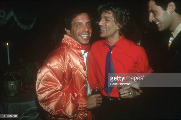 American businessman and Studio 54 nightclub owner Steve Rubell dressed in a quilted salmoncolored satin jacket smiles as he stands and drinks with...