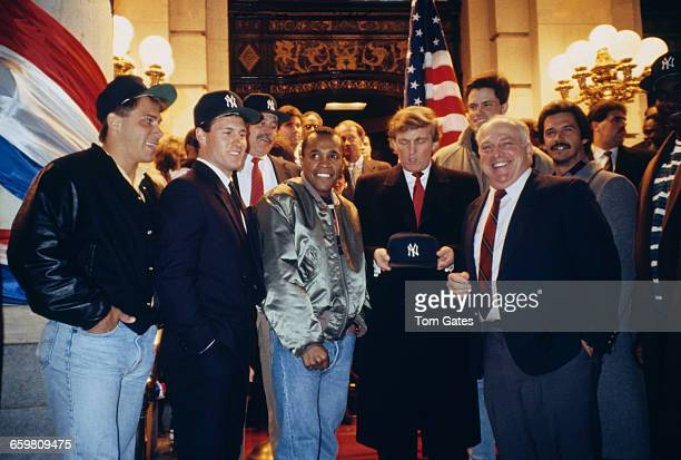 American businessman Donald Trump holding a New York Yankees baseball cap at an event in New York City circa 1990 With him are boxer Sugar Ray...