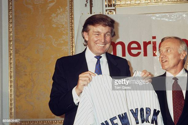American businessman Donald Trump holding a New York Yankees shirt at an event in New York City circa 1990