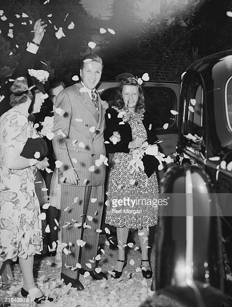American businessman Henry Ford II and his wife Anne McDonnell Ford and her mother Anna Murray McDonnell pause for a photograph under a shower of...