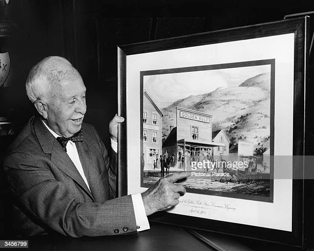 American businessman James Cash Penney owner of the JC Penney chain of retail stores points to a picture of his first store Golden Rule in Kemmerer...