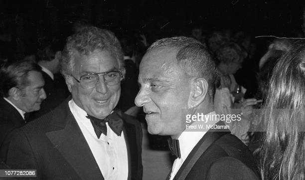 American businessman Victor Potamkin and attorney Roy Cohn smile during Cohn's birthday party at the Seventh Regiment Armory New York New York...