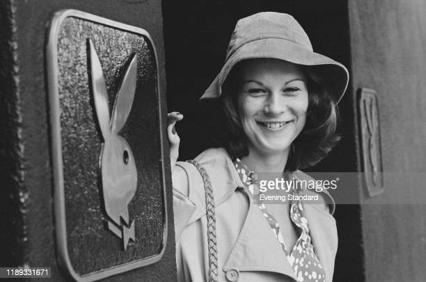 American businesswoman and activist Christie Hefner standing next to a Playboy sign, UK, 26th October 1976.
