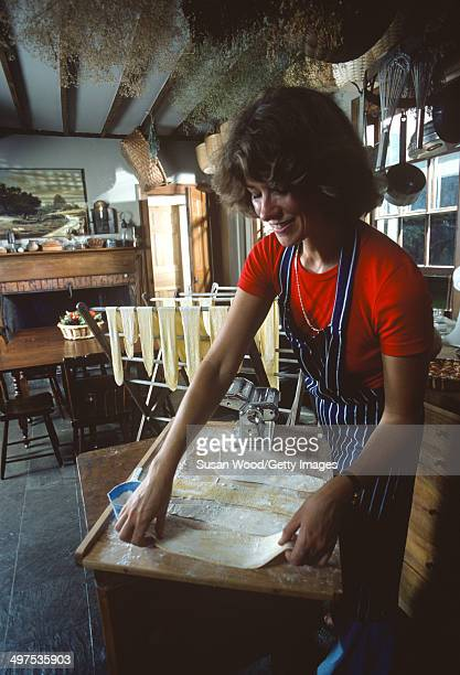 American businesswoman Martha Stewart lays out pasta on a wooden board atop a table in her kitchen Westport Connecticut August 1976