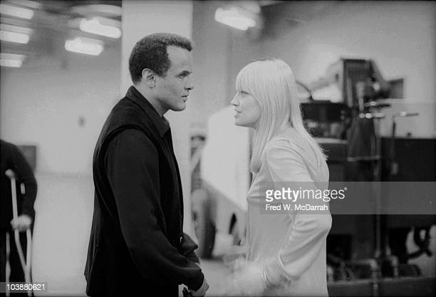 American Calypso singer and Civil Rights activist Harry Belafonte speaks with folk and pop singer Mary Travers backstage at the Winter Concert for...