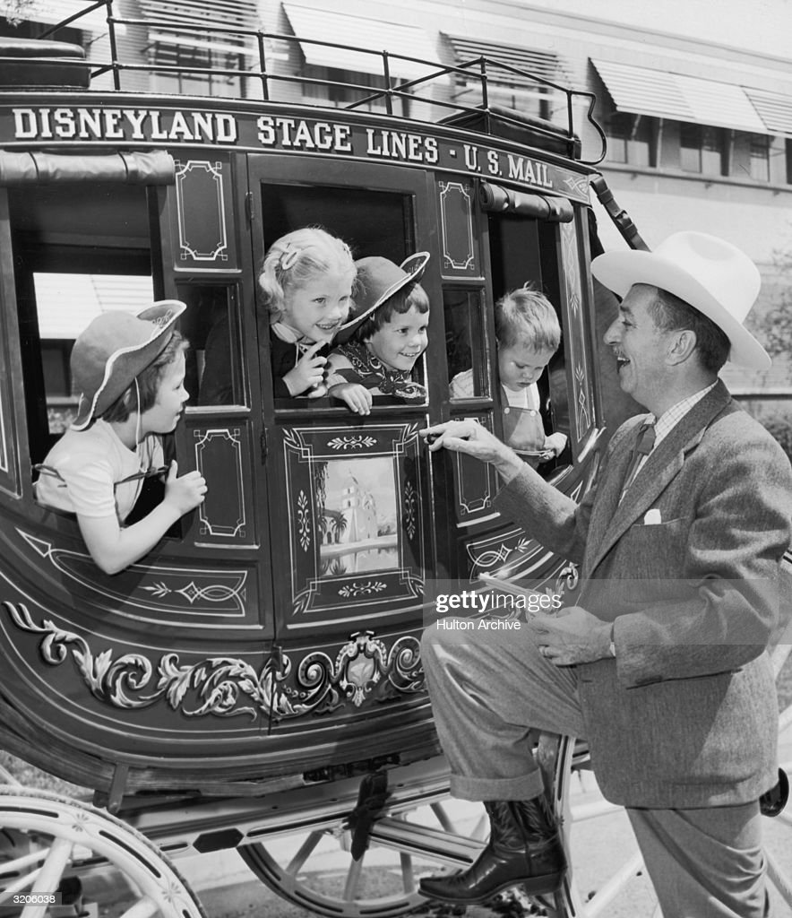 American cartoonist and producer Walt Disney (1901 - 1966), using a toy revolver, smiles while pretending to hold up children in a stagecoach at his Disneyland theme park in Anaheim, California. Disney wears a cowboy hat and boots.