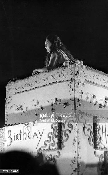 American cellist and performance artist Charlotte Moorman waves from the center of a massive birthday cake at the 8th Avant Garde Festival at the...