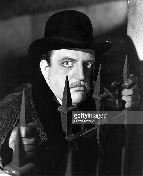 American character actor Laird Cregar is peering through some railings in a scene from 'The Lodger' which incorporates the Jack The Ripper murders...