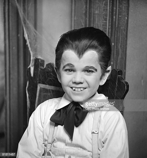 American child actor Butch Patrick sits in a chair and wears an Eton collar and cravat as Eddie Munster a boy werewolf in a promotional ctill from...