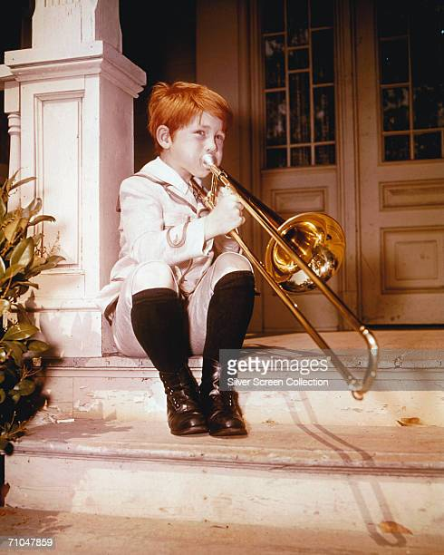 American child actor Ron Howard plays the trombone, circa 1960. As an adult, Howard continued to act in films and on Television, as well as taking up...