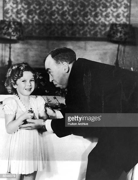 American child actor Shirley Temple receives a special Oscar from American screenwriter Irwin S Cobb at the Academy Awards ceremony Biltmore Bowl...
