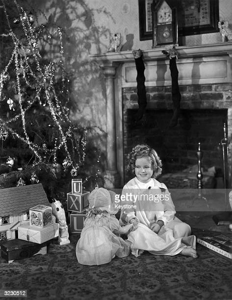 American child actor Shirley Temple sitting by her Christmas tree with presents from 20th Century Fox and a decorated Christmas tree, 1936. Stockings...