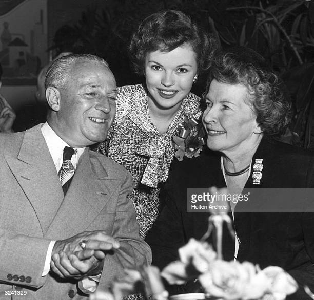 American child actor Shirley Temple smiles while posing with her parents Mr and Mrs George Temple at a party to mark Temple's return to 20th...