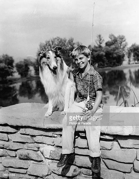 American child actor Tommy Rettig holding a fishing pole sits on the stone wall of a bridge with his arm around Lassie in a promotional portrait for...