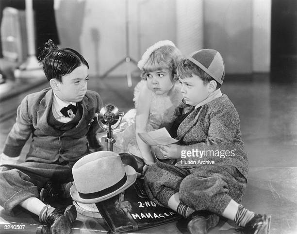 American child actors Carl Switzer Darla Hood and George McFarland sit on the floor around a microphone in a still from director Fred C Newmeyer's...