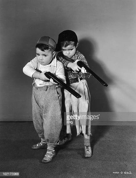 American child actors George 'Spanky' McFarland and Scotty Beckett of the Hal Roach 'Our Gang' and 'Little Rascals' comedy films take aim with toy...