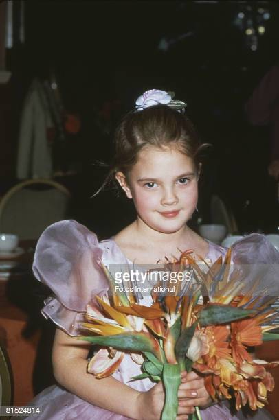 American child actress Drew Barrymore holds a bouquet of flowers as she attends the 40th Annual Golden Globe Awards in support of her film 'ET the...