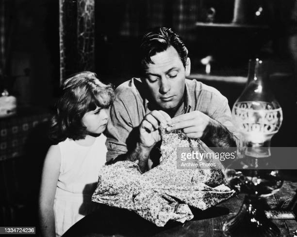 American child actress Mary Jane Saunders watches American actor William Holden sewing in a scene from 'Father Is a Bachelor,' in which Saunders...