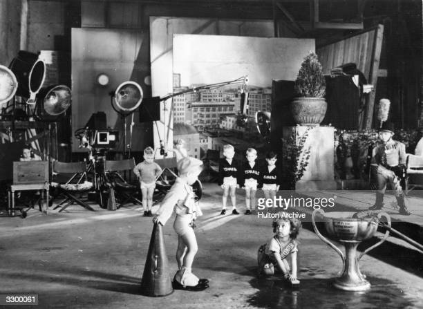 American child star Shirley Temple scrubs the floor of the studio with other children in a scene from the film 'The Kid In Hollywood' directed by...