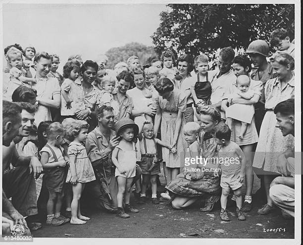American children born in Bilibid Prison concentration camp in Manila pose for a photograph with their mothers and the American soldiers who freed...