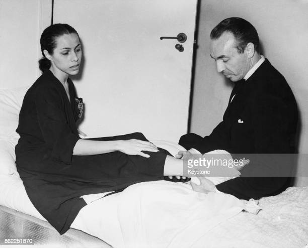 American choreographer George Balanchine checks on his wife Maria Tallchief prima ballerina of the New York City Ballet after she injured her ankle...
