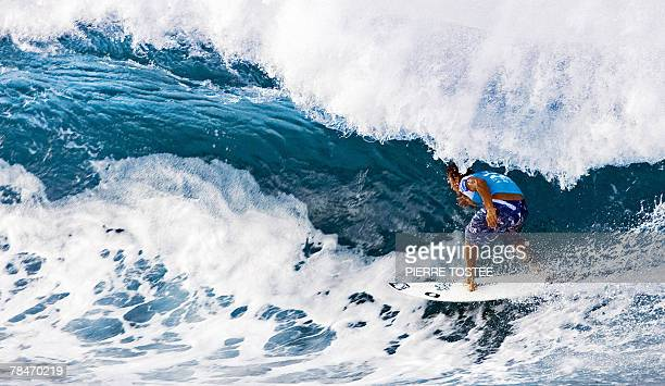 American Chris Ward rides a roll to advance to round three of the Billabong Pipeline Masters 13 December 2007 by beating Hawaiian Shane Dorian in...