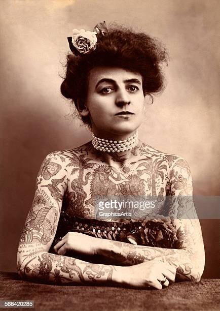 Early photograph of a woman covered with extensive tattoos toned photograph 1907