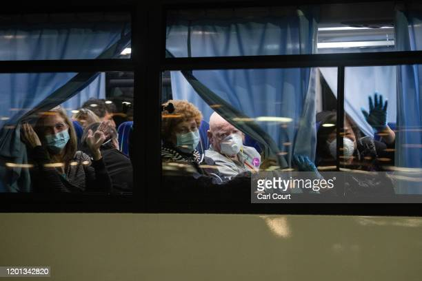 American citizens wave from a bus as they leave the quarantined Diamond Princess cruise ship at Daikoku Pier to be repatriated to the United States...