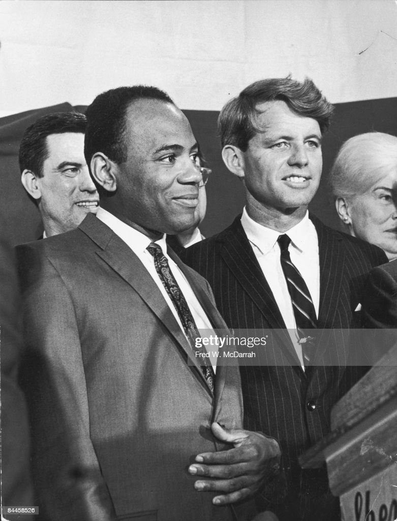American Civil Rights activist and law student James Meredith (with hand on stomach) and United States Senator (and former US Attorney General) Robert F. Kennedy (1925 - 1968) (in pin-stripe suit) stand together on a podium, New York, New York, late June 1966. Recovering from a gunshot wound suffered durign his one-man (at the outset) March Against Fear, Meredith had been the first African-American student to attend (and graduate from) the University of Mississippi; his letters to the then-Attorney General Kennedy eventually let to US troops being sent to Mississippi to quell riots resulting from Meredith's registration. Here, the pair pose together likely at a Sheraton hotel during their endorsement of Democratic candidate Samuel Silverman for Manhattan Surrogate Court.