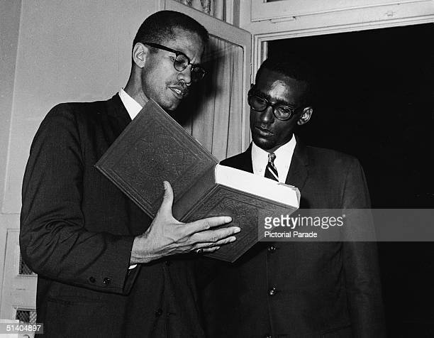 American civil rights activist and ousted leader of the Black Muslims Malcolm X points out quotations from the muslim holy book The Koran to make a...