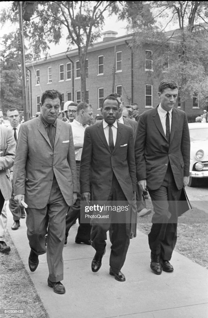 American Civil Rights activist and student James Meredith (center) is escorted by Chief US Marshal James JP McShane (1909 - 1968) (left) and Assistant Attorney General for Civil Rights John Doar (1921 - 2014), along with others, on his way to register for classes at the University of Mississippi, Oxford, Mississippi, October 1, 1962.