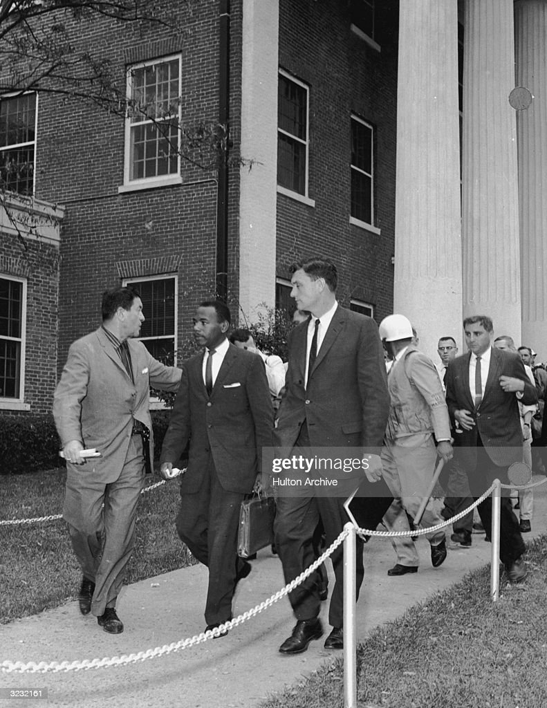 American civil rights activist James Meredith and attorney Joan Doar (1921 - 2014) are escorted by Federal Marshals as they enter the all-white University of Mississippi.