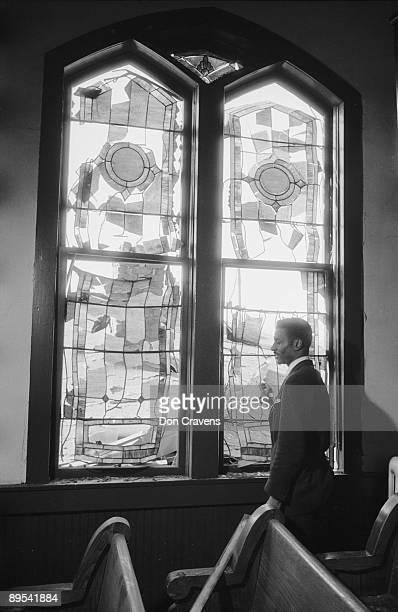 American Civil Rights activist Reverend Fred Shuttlesworth stands next to a stainedglass window smashed during the Mongomery Bus Boycott Montgomery...