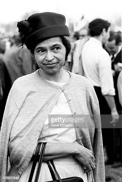 American civil rights activist Rosa Parks wearing a dark hat, a cardigan over her shoulders, with her arm looped through the straps of a handbag,...