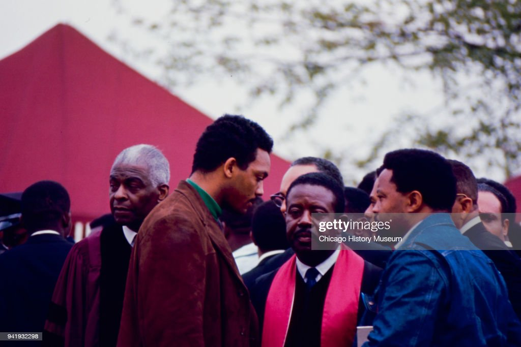American Civil Rights and religious leaders Benjamin May (1894 - 1984) (at left, in maroon robe), Jesse Jackson (in green turtleneck) and Ralph Abernathy (1926 - 1990) (center) stand with unidentified others during Dr Martin Luther King Jr's burial service at South View Cemetery, Atlanta, Georgia, April 9, 1968.
