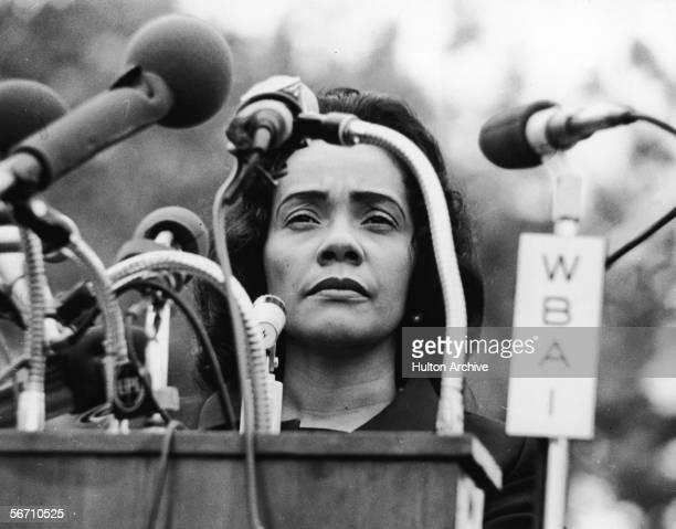 American civil rights campaigner and widow of Dr Martin Luther King Jr Coretta Scott King stands behind a podium covered in microphones at...