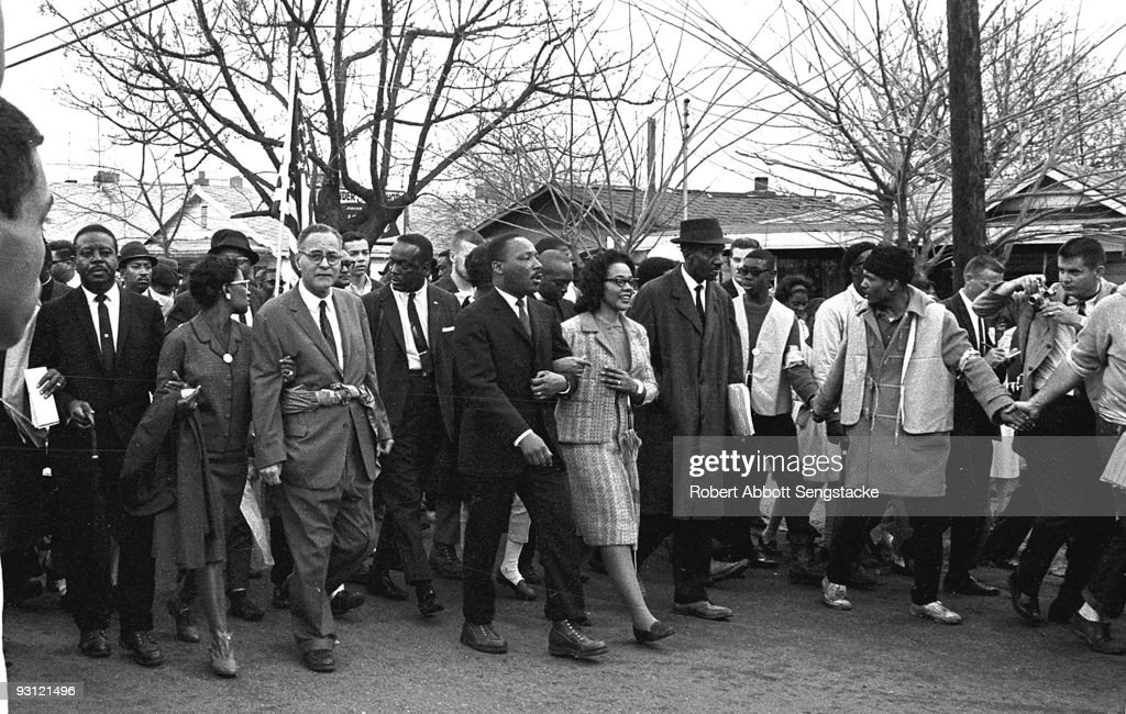 American Civil Rights leader Dr. Martin Luther King Jr. (1929 - 1968) and his wife Coretta Scott King (1927 - 2006) (center, arm in arm) lead others during on the Selma to Montgomery marches held in support of voter rights, Alabama, late March, 1965. Among those with them are Reverend Ralph Abernathy (1926 - 1990) (at left, facing camera), and Pulitzer-Prize winning political scientist and diplomat Ralph Bunche (1904 - 1971) (front row, third left with glasses) whose his wife, Ruth (nee Harris, 1906 - 1988), holds his arm.