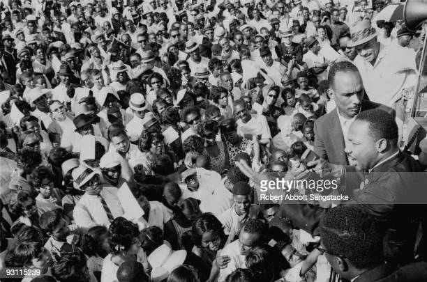 American Civil Rights leader Dr. Martin Luther King Jr. Is helped through a massive crowd during a Chicago Freedom Movement rally in Grant Park,...