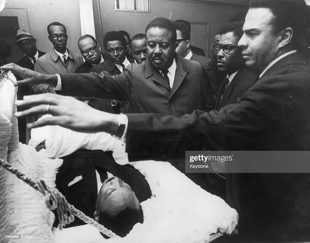 American civil rights leader Dr Martin Luther King Jr. (1929 - 1968) lying in state in Memphis, Tennessee, as his colleagues pay their respects to him (right to left); Andrew Young, Bernard Lee and Reverend Ralph Abernathy (1926 - 1990).