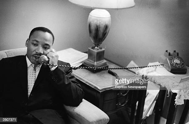American civil rights leader Dr Martin Luther King Jr sits on a couch and speaks on the telephone after encountering a white mob protesting against...