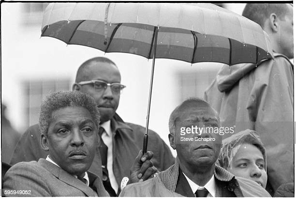 American Civil Rights leaders Bayard Rustin and A Philip Randolph stand under an umbrella they listen to a speech on steps of the Alabama State...